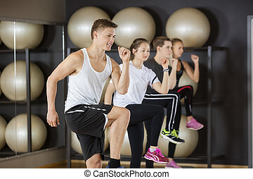 Man Doing Step Exercise With Friends In Gym