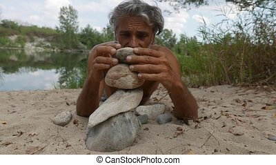 man doing stone balancing along the river