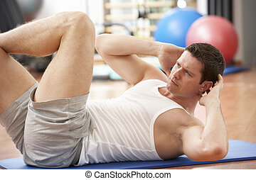 Man Doing Stretching Exercises In Gym