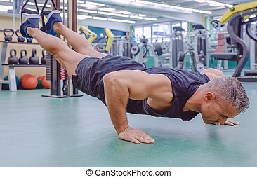 Man doing suspension training with fitness straps - Handsome...