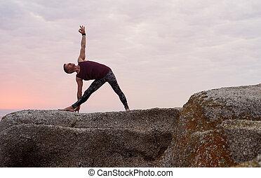 man doing the eagle pose on rocksa waterfall fit man