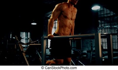 man doing triceps dip exercise on bars in dark gym