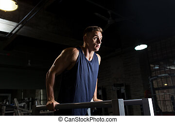 man doing triceps dip on parallel bars in gym
