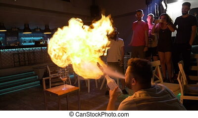 Man doing trick spraying vodka flame from bottle sets on fire stack of glasses