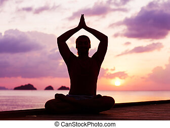 man doing yoga at sunset