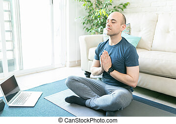 Man doing yoga from a laptop at home