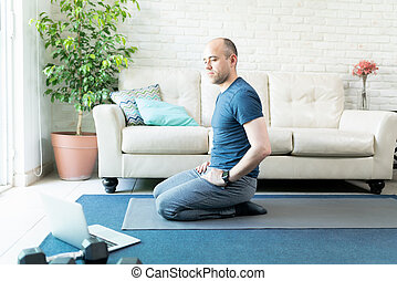 Man doing yoga from a laptop computer at home