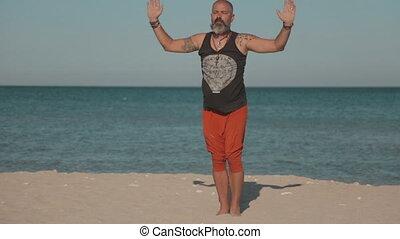Man doing yoga near the sea