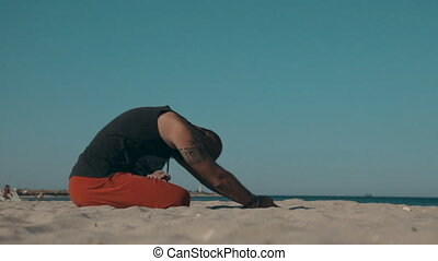 Man doing yoga on the shore of the beach