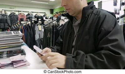 man, dokt, geld, in, contant, in, de, de opslag van de kleding, winkel