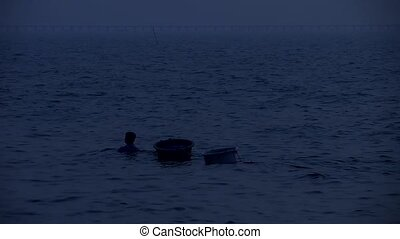 man drag two basin of fine seafood after sunset