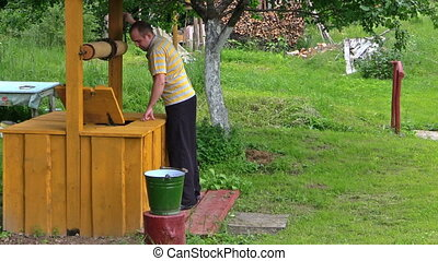 man draw water well - young worker draw full bucket water...
