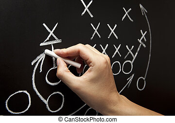 Man drawing a game strategy with white chalk on a blackboard...