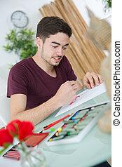 man drawing a sketch at home