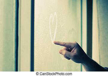 man drawing hearts in wet window