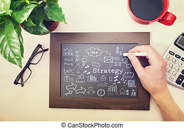 Man drawing strategy cartoon on chalkboard