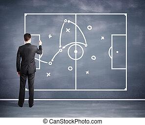 man drawing tactic scheme on big black desk board