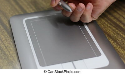 Man draws a pen on tablet lying on