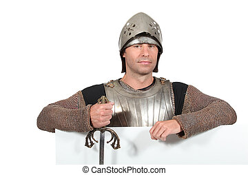 Man dressed as a knight with a board left blank for your message