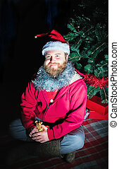 Man Dressed As Santa Sitting Under The Christmas Tree