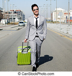 Man dressed in suit and suitcase walking along the street -...