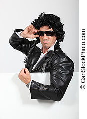 Man dressed up in a silly wig and biker jacket standing with a board left blank for your image