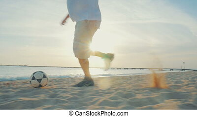 Man dribbling on the beach at sunset