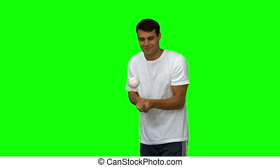 Man dribbling with a baseball on green screen in slow motion