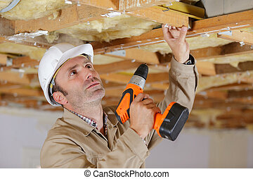 man drilling a hole in white ceiling