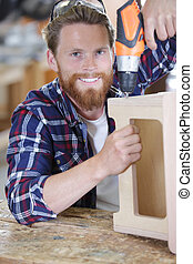 man drilling furniture wood