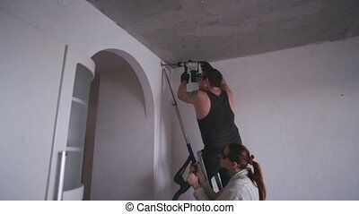 Man drills a hole in the wall with a puncher. A woman cleans...