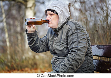 Man drink beer from bottle in the park