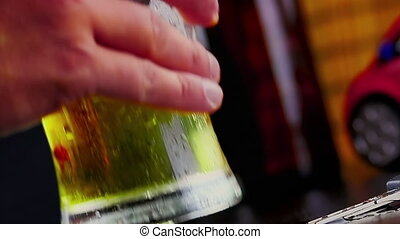 man drink fresh beer with foam in front of beer bottles and...