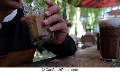 man drink glass of iced coffee from a paper straw at cafe. Slow motion shot