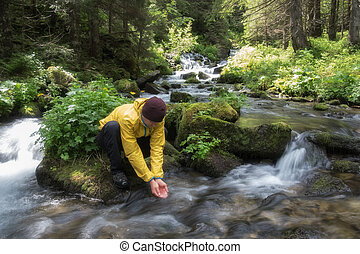 Man drink water from clear mountain stream in the lush...
