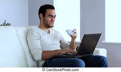 Man drinking a coffee while using a laptop