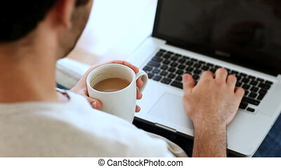 Man drinking a coffee while using laptop