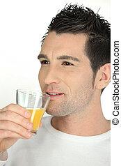 Man drinking a glass of orange juice