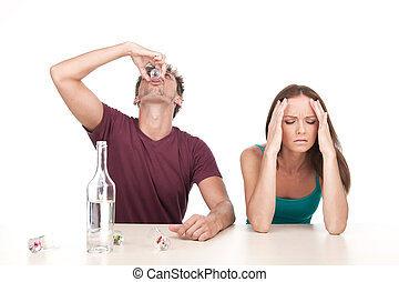 Man drinking alcohol and woman sitting upset at table. Photo...