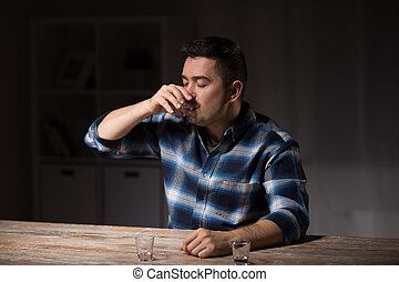 man drinking alcohol at night