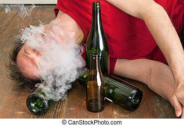 man drinking and smoking - man lying on floor drinking...