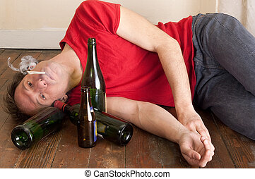 man drinking and smoking - young man lying on floor smoking...