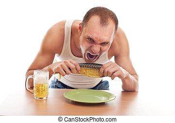 man drinking beer and eatin fish