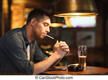 people, smoking and bad habits concept - man drinking beer and lighting cigarette at bar or pub