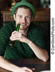 man drinking beer from green bottle at bar or pub - people,...
