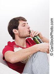Man drinking beer on a couch