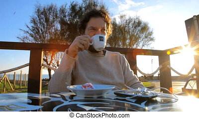 man drinking cappuccino reading - happy young man outdoor...