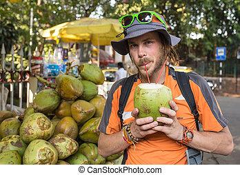 Man drinking coconut milk