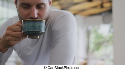 Man drinking coffee at dining table in a comfortable home 4k
