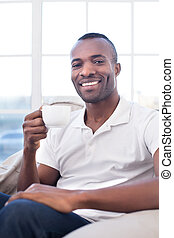 Man drinking coffee. Cheerful African man drinking coffee and smiling